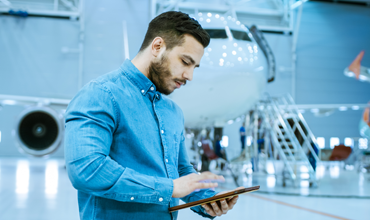 Man with tablet in airplane hangar