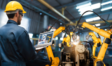 Assembly worker using laptop to control robotic arm assembly line